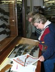 A lady examines a mint condition old advertising poster announcing the introduction of the Rey Ryder Carbine that was sold at a silent auction during the activities.