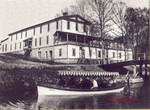 A gondola, loaded with visitors, pulls away from the dock at the Monte Ne Hotel in this July 4, 1907 photograph. The launch is headed for the ampitheatre. This is a seldon seen side of the hotel in original photographs. The photograps is from the private collection of Jerry Hiett.