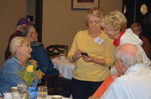 Judy Allen, Mary Lou Creech, and Sherry (Coffman) Solomon find a picture of someone amusing.