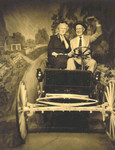 "Leon Garrett ""Garry"" and Rose Perrine (Thorpe) Griggs take a Sunday Outing in a then-new automobile through a photo studio."