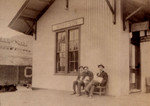 "Jacob ""Peepa"" Weisser (at right) waits on the platform of the Morrison, CO, depot for the train back to Denver. the sign over the door at far right advertizes the Western Union Telegraph office. The resort hotel of Morrison can be seen above the train cars.